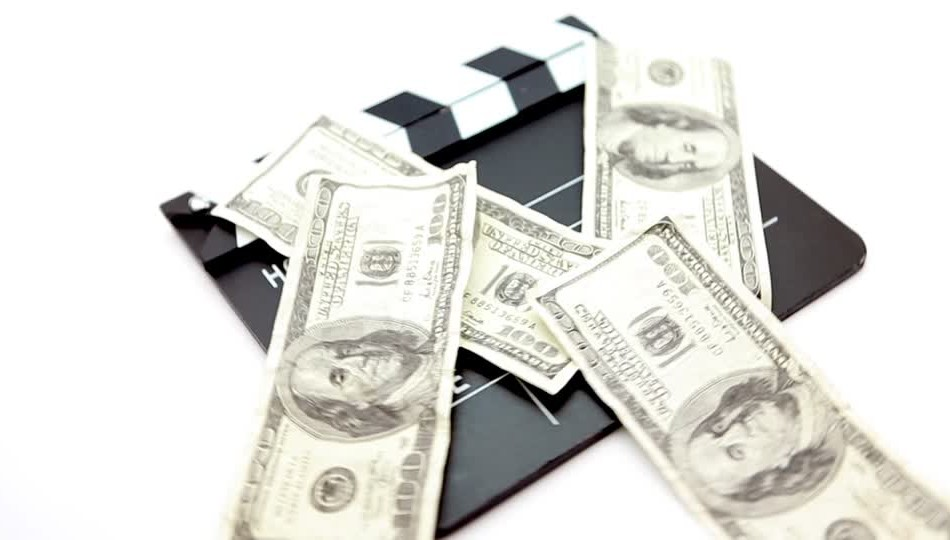 357347053-clapboard-bundle-of-money-fanning-us-dollar